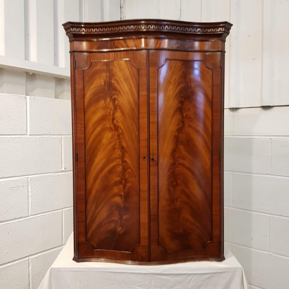 antique flamed mahogany serpentine front hanging corner cabinet c1920
